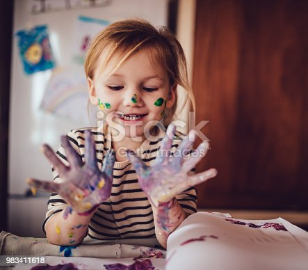 983418152istockphoto Happy little girl with dirty hands finger painting at home 983411618