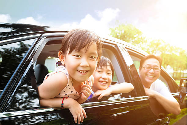 happy little girl with family sitting in the car - asian travel in car stock photos and pictures