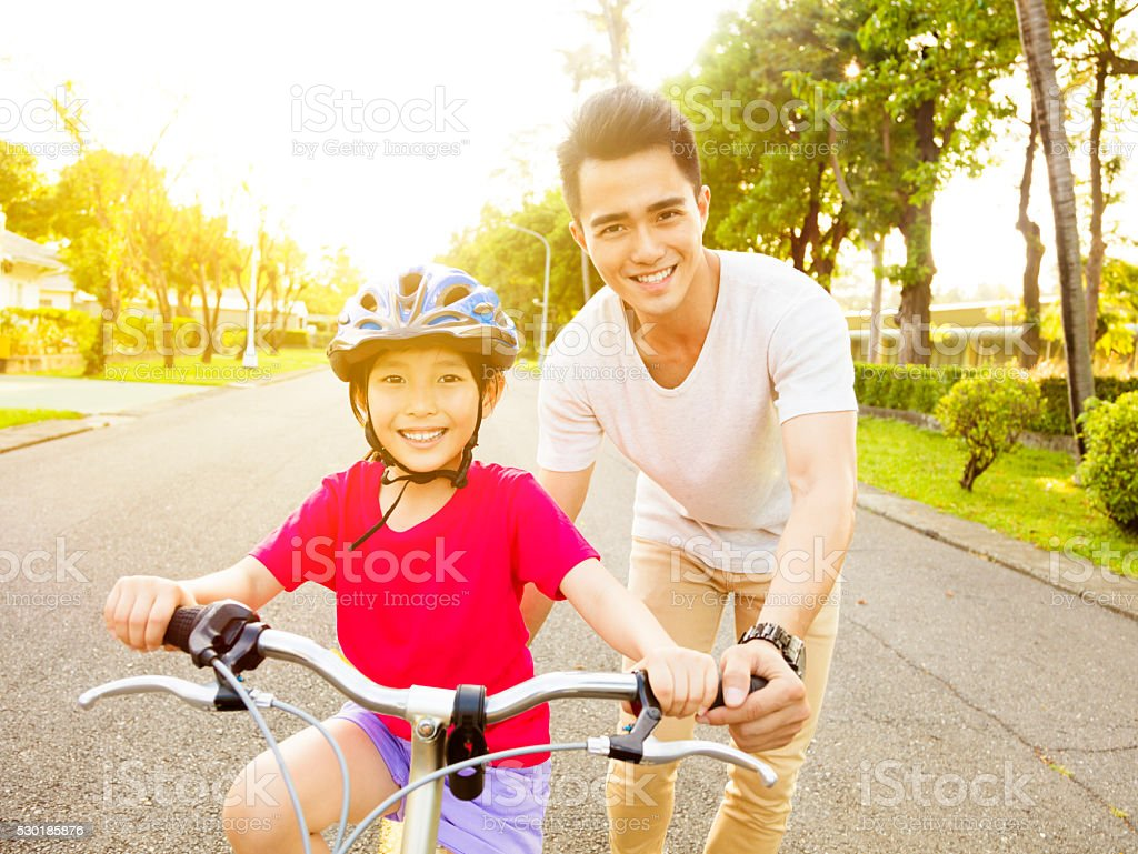 happy little girl with father practice to riding  bicycle stock photo