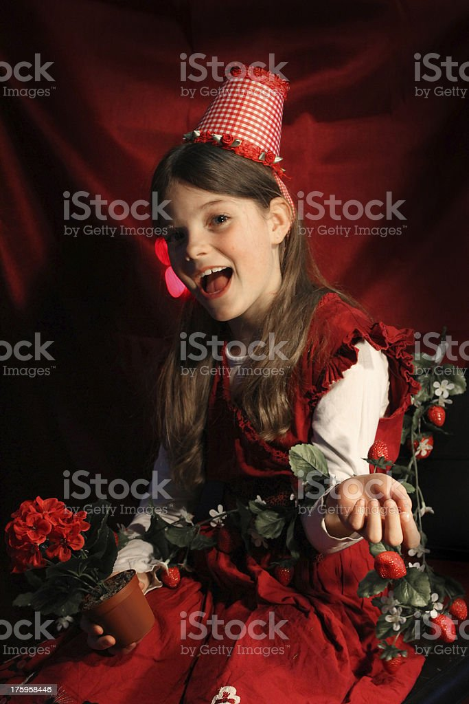 Happy little girl with flowers and strawberries royalty-free stock photo
