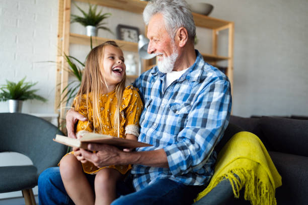 Happy little girl with grandfather reading story book at home stock photo