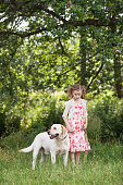 istock Happy little girl with her dog labrador on a walk in summer nature. 1137369332