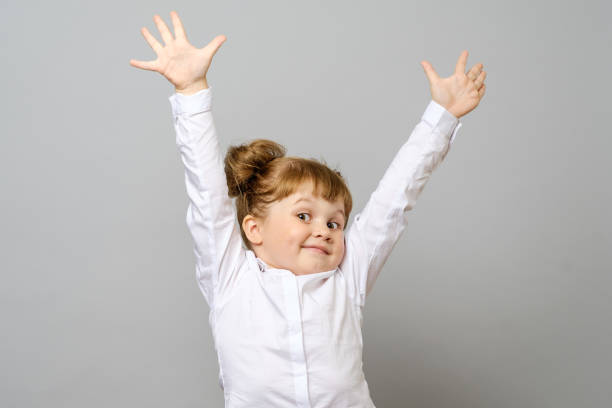 Happy little girl with her hands up isolated stock photo