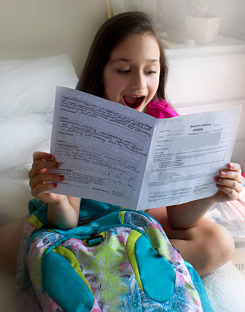 Happy little girl with her report card. stock photo