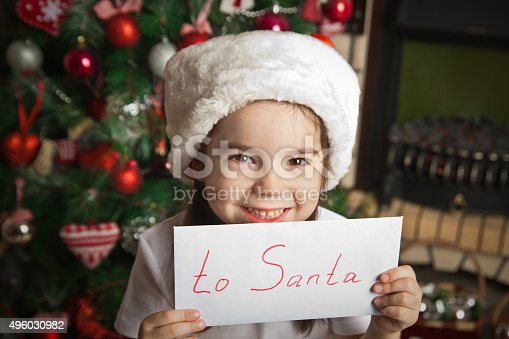 1062609644istockphoto Happy little girl with letter to Santa near christmas tree 496030982