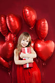 Happy little girl with red balloons and birthday gift on balloons party celebration background. Pretty child birthday party lifestyle portrait