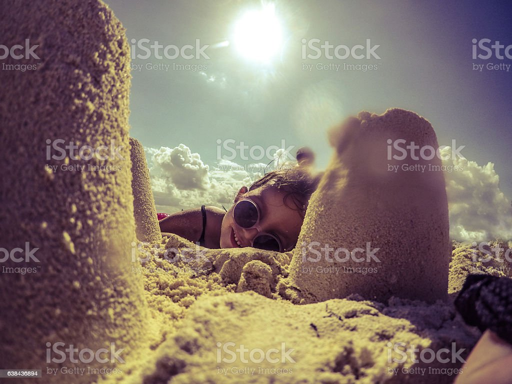 Happy little girl with sunglasses playing with sand on beach stock photo
