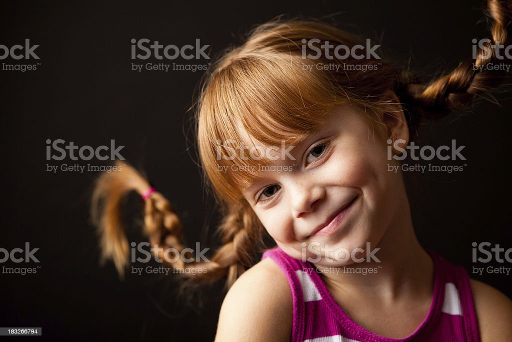 Happy Little Girl with Upward Braids on Black Background royalty-free stock photo