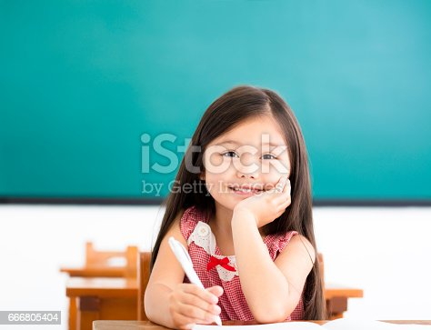 istock happy little girl writing at desk in classroom 666805404