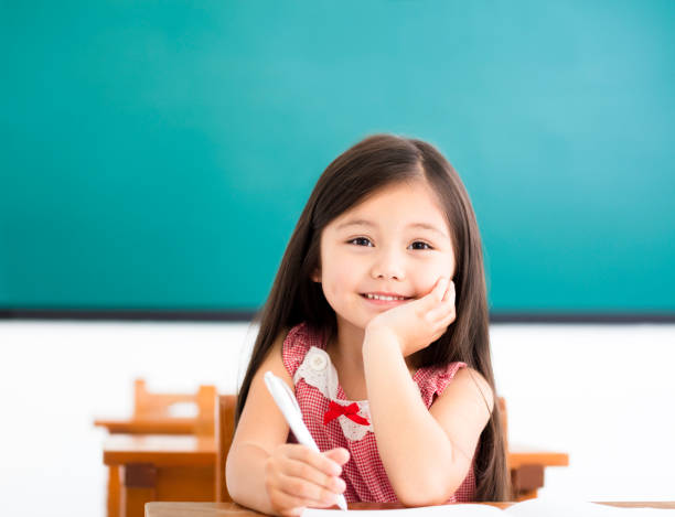 happy little girl writing at desk in classroom stock photo