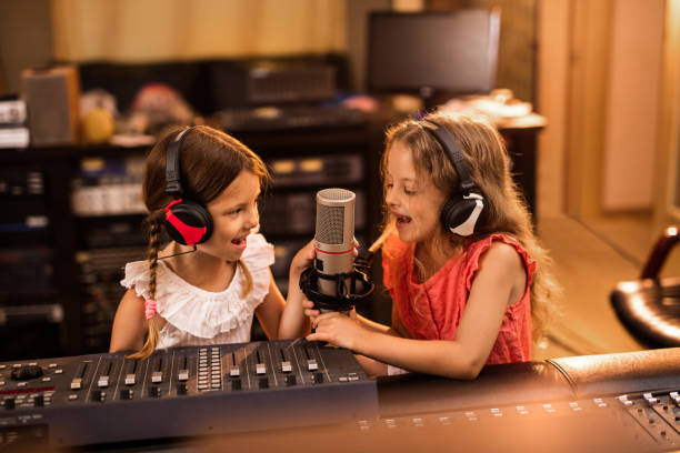 happy little girls broadcasting a radio show from the station. - radio dj stock photos and pictures