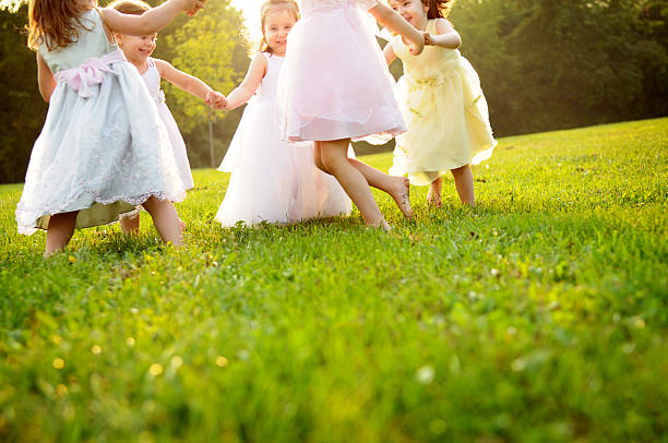 Happy Little Girls Dancing in a Circle Outside stock photo