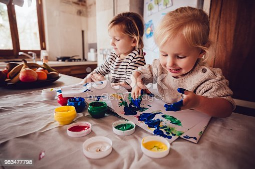 983418152 istock photo Happy little girls drawing with paint in family house kitchen 983477798