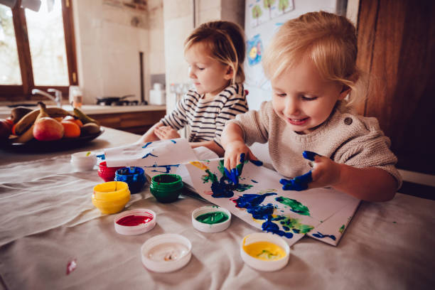 Happy little girls drawing with paint in family house kitchen stock photo