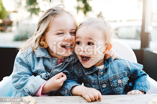 Happy Sisters Laughing While Sitting Together Outside
