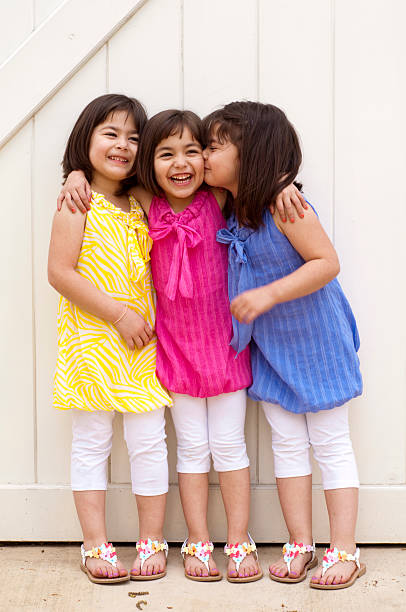 happy little girls in spring colors - triplets stock photos and pictures
