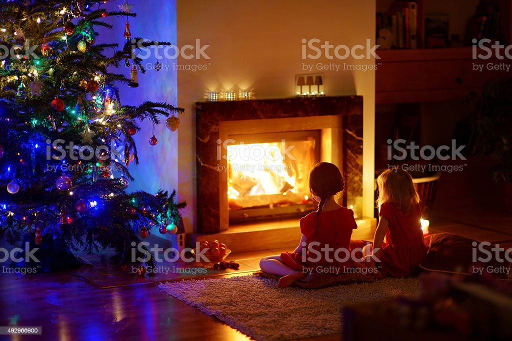 Happy little girls sitting by a fireplace on Christmas eve stock photo