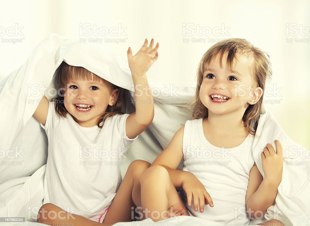 happy little girls twins sister in bed under the blanket royalty-free stock photo
