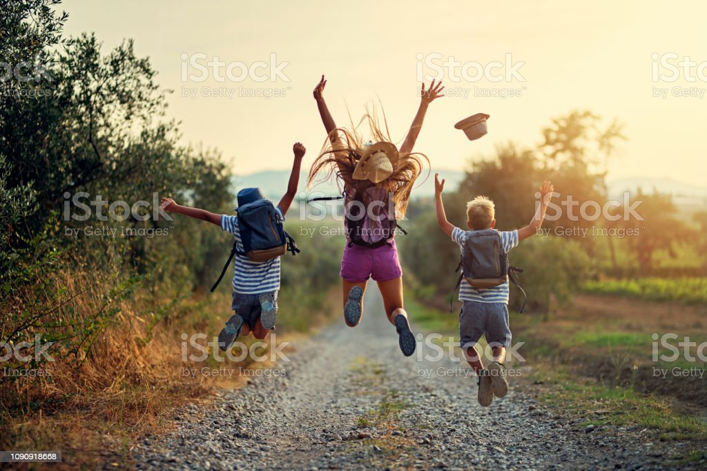 Happy little hikers jumping with joy Brothers and sister hiking in Tuscany, Italy. Kids are jumping with joy on dirt road. Nikon D850 Accuracy Stock Photo