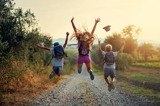 Happy little hikers jumping with joy Brothers and sister hiking in Tuscany, Italy. Kids are jumping with joy on dirt road. Nikon D850 mid air stock pictures, royalty-free photos & images