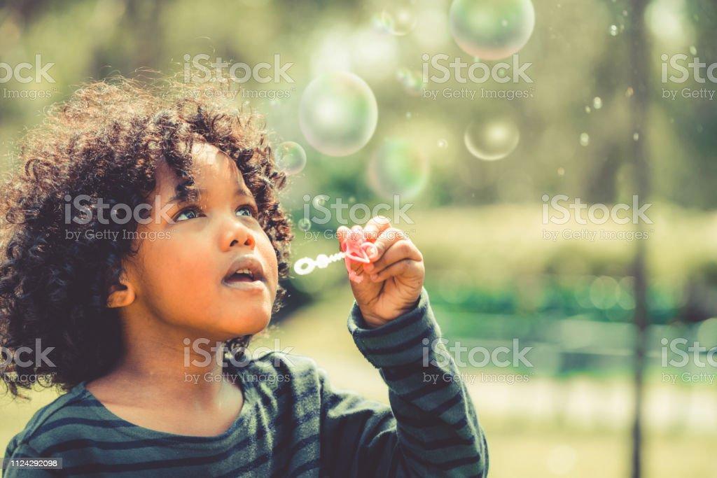 Glückliches kleines Kind Seifenblase im Schulgarten. – Foto