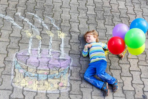 glückliche junge kind spaß mit großen geburtstag kuchen bild zeichnung mit farbigen kreiden und luftballons. kreative freizeit für kinder im freien im sommer. - vorschulgeburtstag stock-fotos und bilder