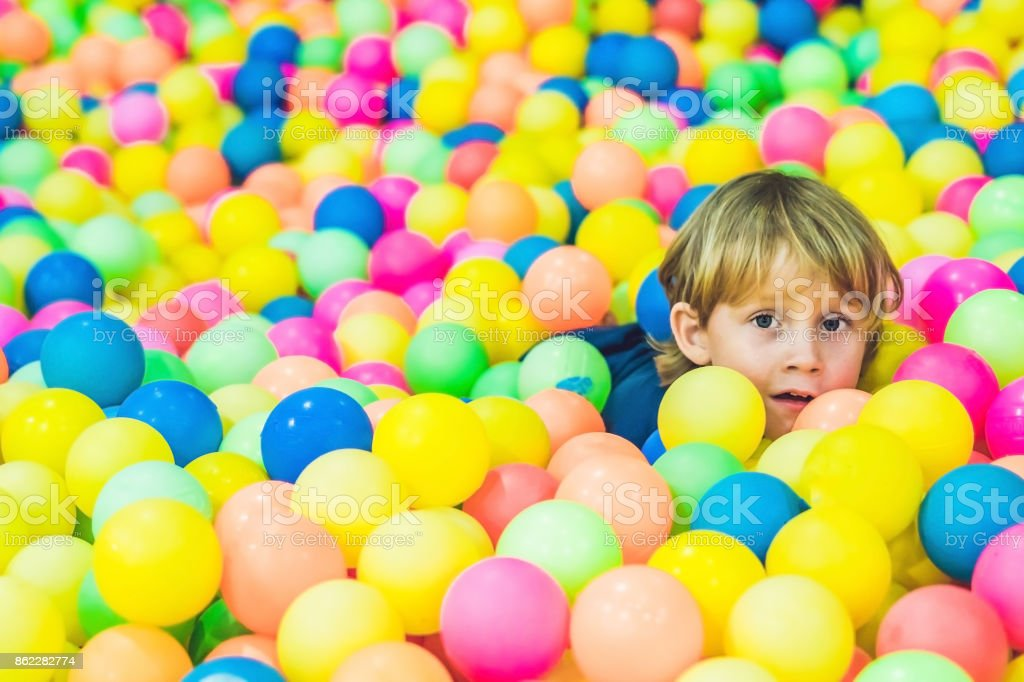Happy little kid boy playing at colorful plastic balls playground high view. Funny child having fun indoors stock photo