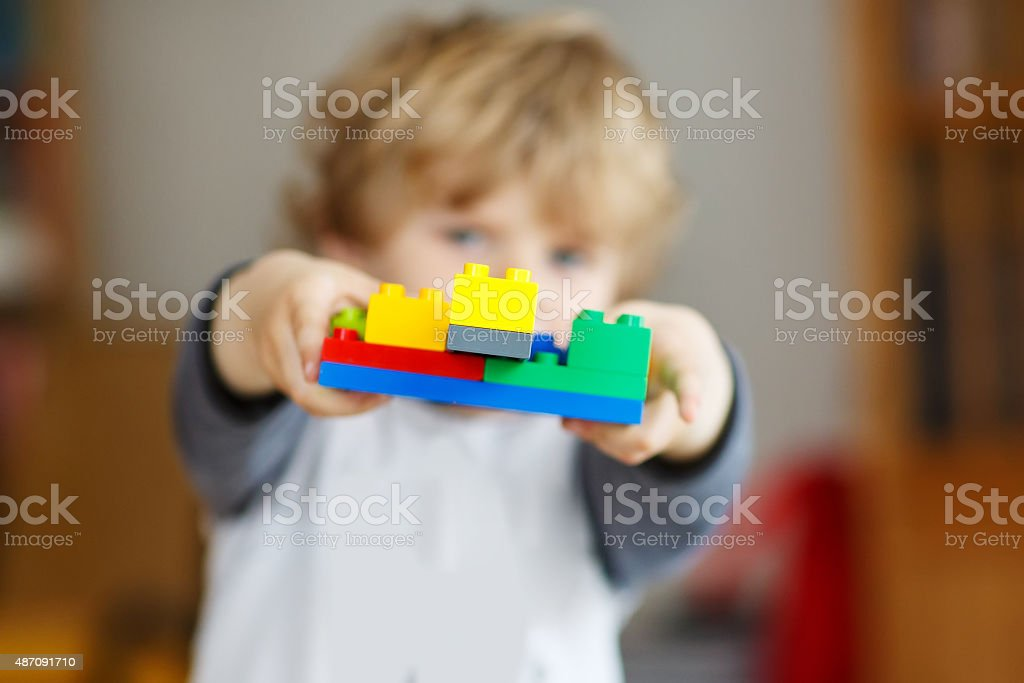 Happy little kid boy playing with construction blocks with creat stock photo