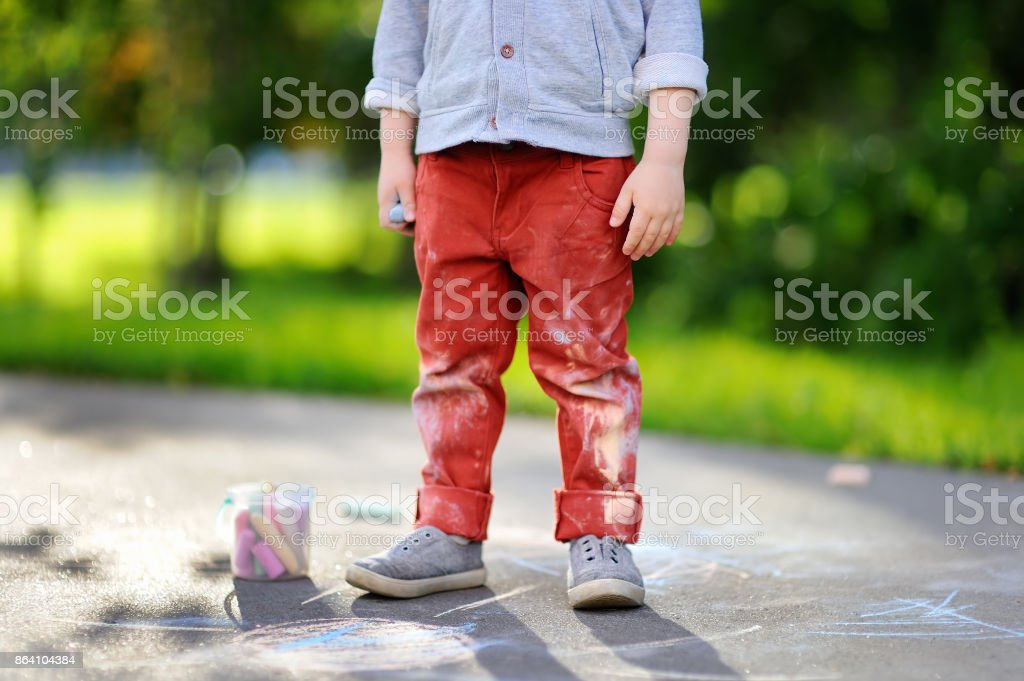 Happy little kid boy sitting and drawing with colored chalk on asphalt royalty-free stock photo