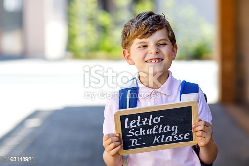 istock Happy little kid boy with backpack or satchel. Schoolkid on the way to school. Healthy adorable child outdoors On desk Last day second grade in German. School's out 1163148921
