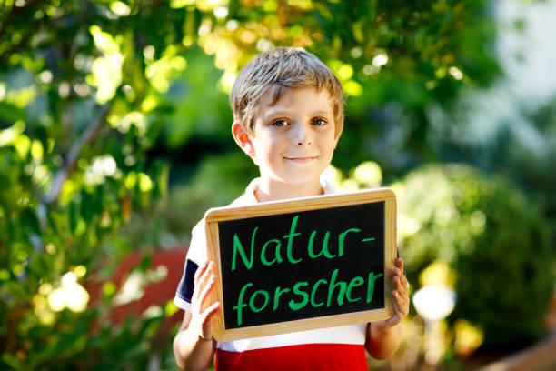 glückliche kleine kind junge mit kreide schreibtisch in händen. gesunden entzückenden kind im freien auf schreibtisch - naturforscher - deutsch als traumberuf des schönen schulkind - abschiedswünsche stock-fotos und bilder