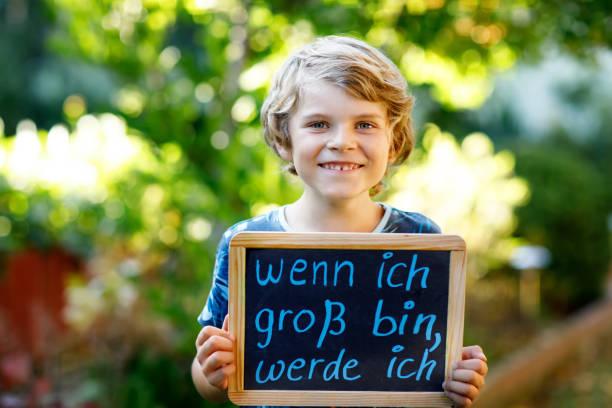 glückliche kleine kind junge mit kreide schreibtisch in händen. gesundes entzückenden kind im freien auf schreibtisch, wenn ich groß bin, ich will in deutsch mit traumberuf sein - abschiedswünsche stock-fotos und bilder