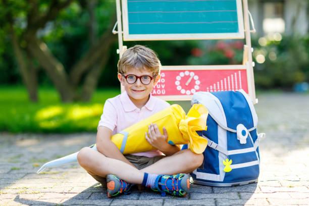 glückliche kleine kind junge mit brille sitzen durch schreibtisch und rucksack oder umhängetasche - liebeskind umhängetasche stock-fotos und bilder