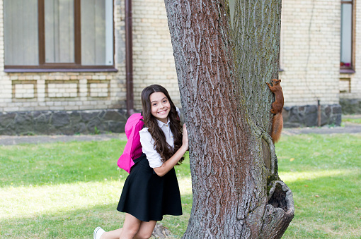 Happy little kid in school uniform with backpack observe squirrel climbing tree in park, outdoor education.
