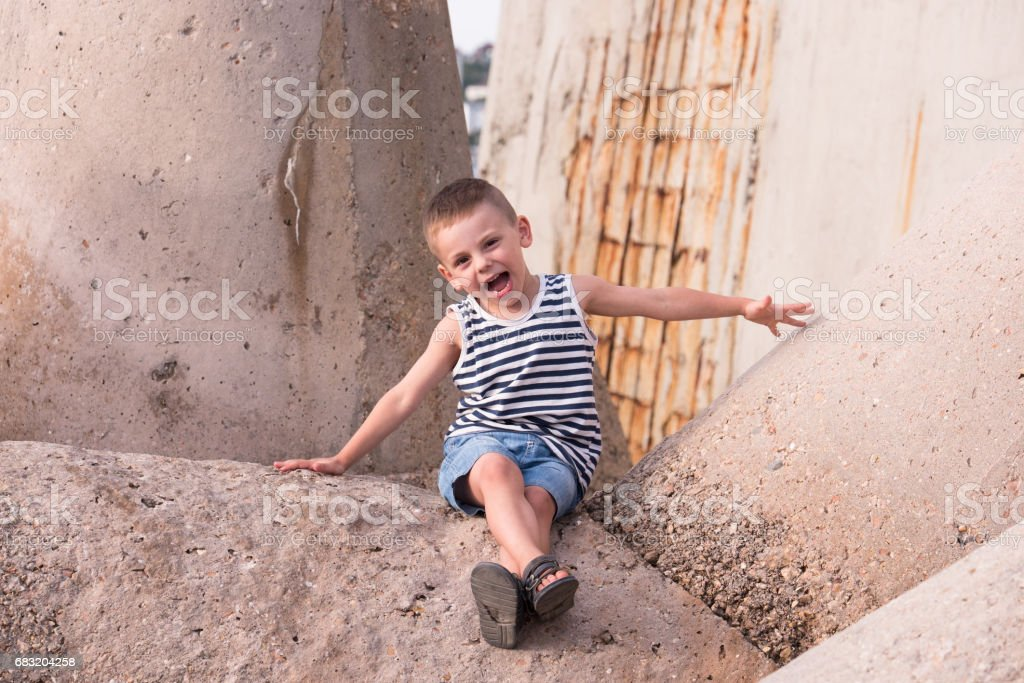 happy little kid sitting on concrete breakwater royalty-free stock photo