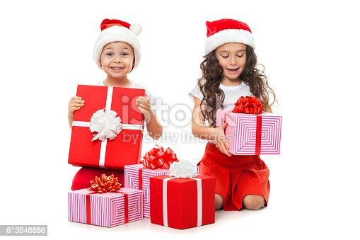istock Happy little kids in Santa hat with Christmas gift boxes 613548886
