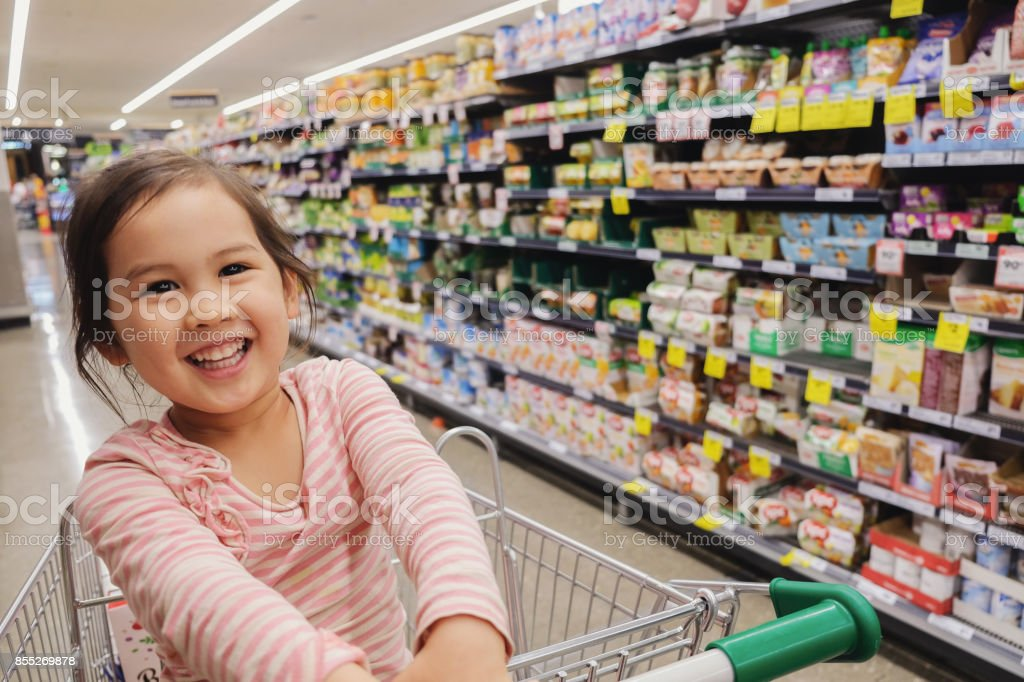Happy little multiethnic girl sitting in a trolley, shopping cart at supermarket, grocery store stock photo