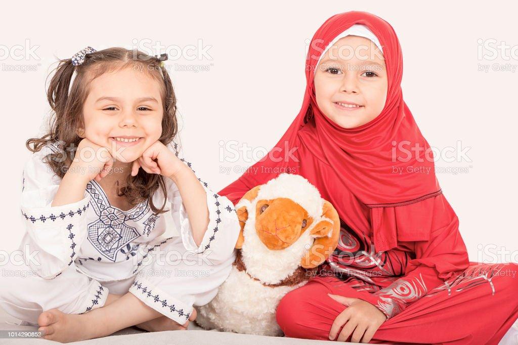 Happy little Muslim girls family celebrating Eid ul Adha stock photo