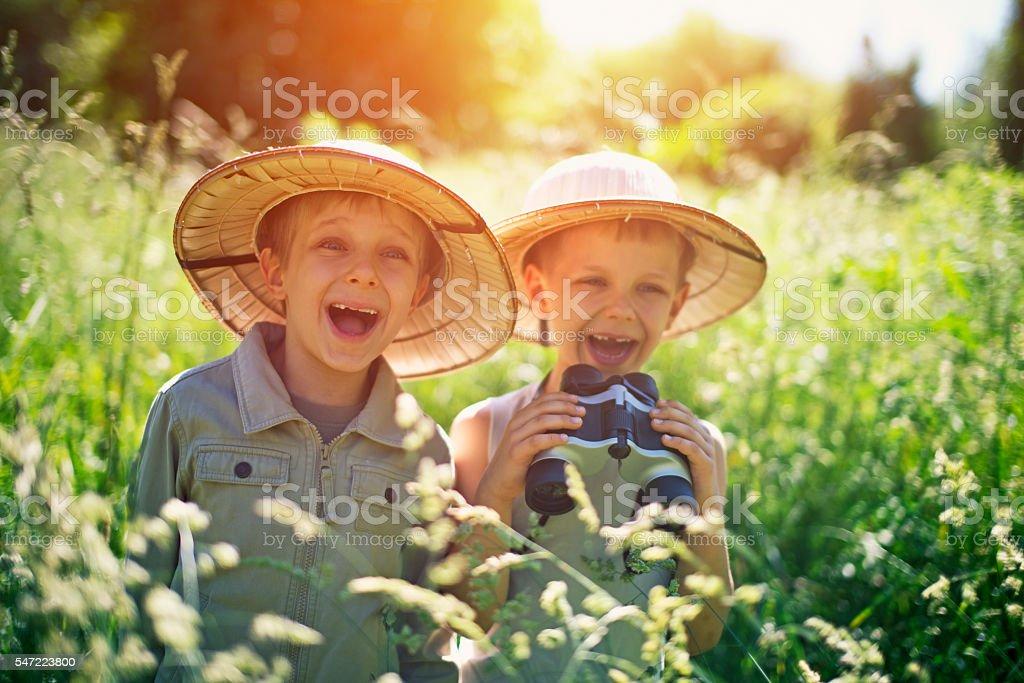 Happy little safari boys exploring widerness stock photo