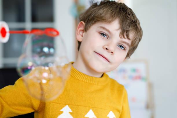 glückliche kleine schuljunge spielt mit seifenblasen zu hause. kind mit spaß. - versuche nicht zu lachen stock-fotos und bilder