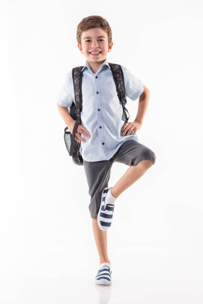 Happy little schoolboy standing isolated on white background stock photo