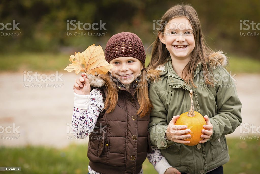 Happy Little Sisters Holding Pumpkin and Autumn Leaf royalty-free stock photo