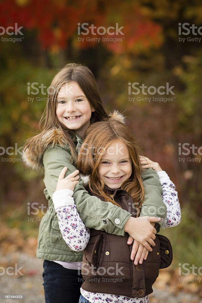 Happy Little Sisters Standing Outside on Fall Day stock photo