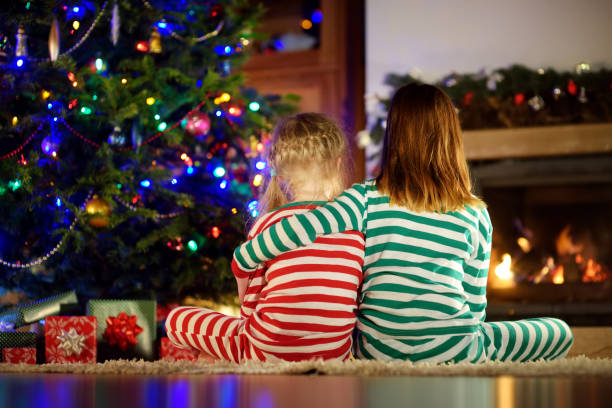 Happy little sisters wearing Christmas pajamas opening gift boxes by a fireplace in a cozy dark living room on Christmas eve. stock photo