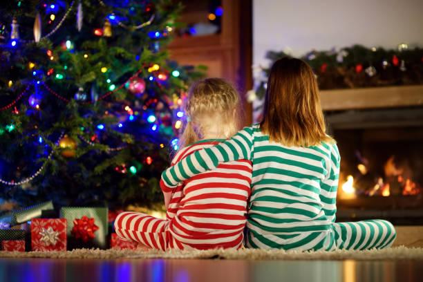 Glückliche kleine Schwestern tragen Weihnachts-Pyjamas öffnen Geschenk-Boxen an einem Kamin in einem gemütlichen dunklen Wohnzimmer an Heiligabend. – Foto