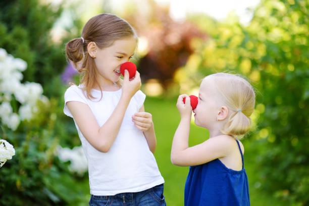 Glückliche kleine Schwestern tragen rote Clown Nasen – Foto
