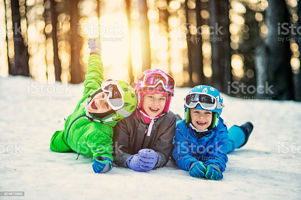 Happy little skiers lying on ski slope stock photo