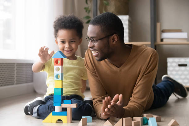 Happy little son playing with black dad using wooden blocks Happy cute little son playing game with black dad baby sitter building constructor tower from multicolored wooden blocks, african family father and toddler child boy having fun on warm floor at home genderblend stock pictures, royalty-free photos & images