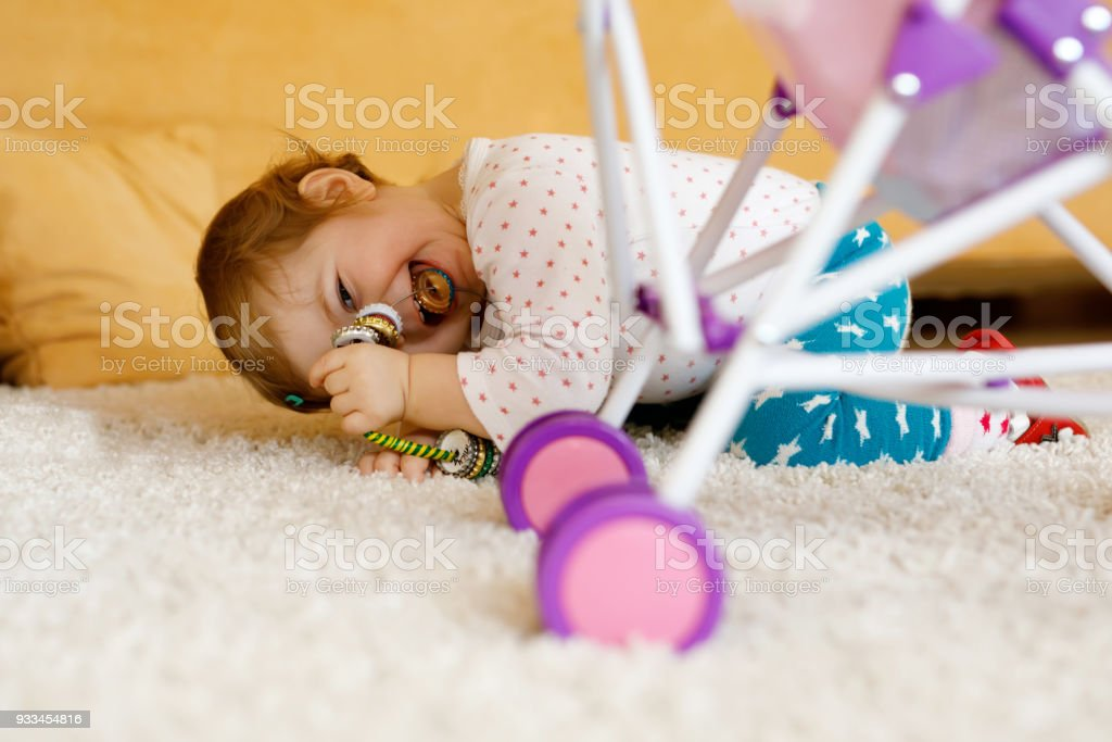 Happy little toddler baby girl playing hide and seek at home. Child having fun with parents or siblings stock photo