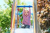 Happy little toddler blond girl having fun sliding on playground